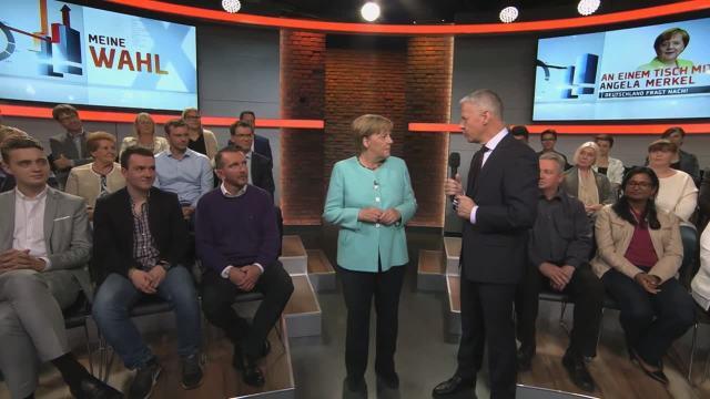 An einem Tisch mit Angela Merkel